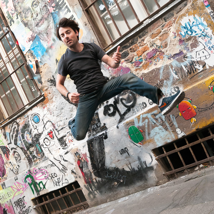 Patrick jumping in front of some collage at a courtyard next to Hackesche Höfe.